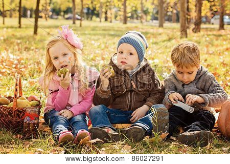 Three Happy Children Playing In Autumn Park With Fruits