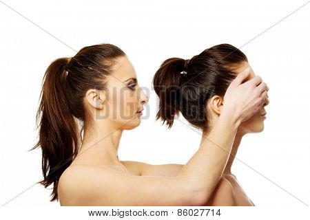 Spa woman covering friend's eyes.