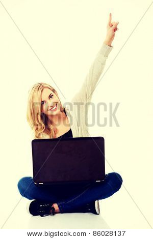 Smiling young woman using a laptop and pointing on copy space