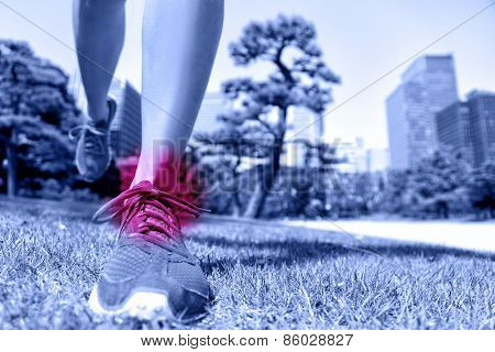 Sports injury - runner feet with ankle pain. Closeup of running shoes landing on soft grass with red circle showing hurting joints and ligaments caused by a fitness trauma.