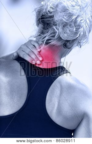 Hurting neck - female runner showing pain with red circle. Athletic running woman with injury in sportswear rubbing touching upper back muscles outside after exercising and training.