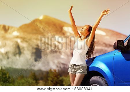 Happy free woman next to car relaxing on summer road trip adventure travel with open arms up showing freedom. Nature travel concept with mountain background in the USA. Young Asian adult driver.
