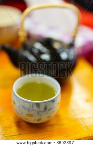 Japanese green tea in a cup with teapot on background