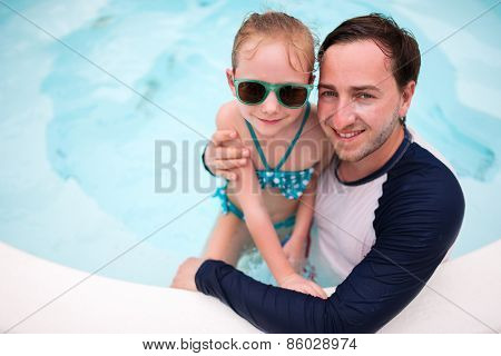 Happy family father and his adorable little daughter at outdoors swimming pool