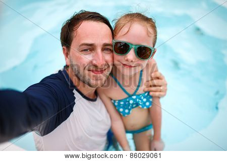 Happy family father and his adorable little daughter at outdoors swimming pool making selfie