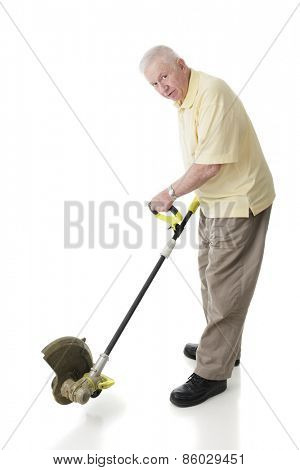 A senior adult man looking at the viewer while demonstrating how a weed whacker is used for edging.  On a white background.