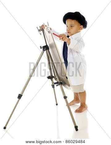 An adorable preschooler concentrating as he paints on an easel in his smock and French beret.  On a white background.