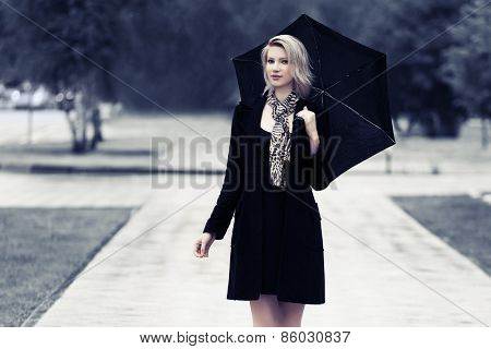 Happy young fashion woman with umbrella walking in the rain