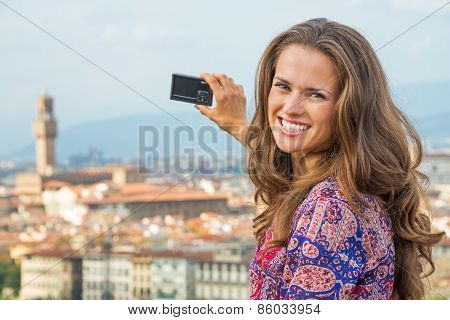 Smiling Young Woman Taking Photo Of Panoramic View Of Florence,
