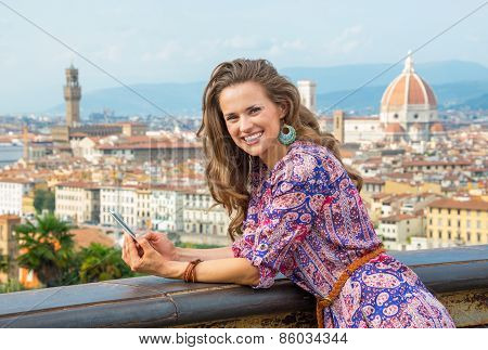 Happy Young Woman Holding Cell Phone Against Panoramic View Of Florence, Italy