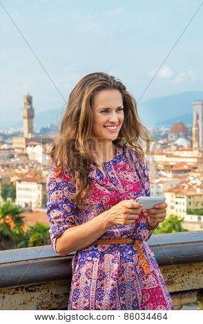 Happy Young Woman Writing Sms Against Panoramic View Of Florence, Italy