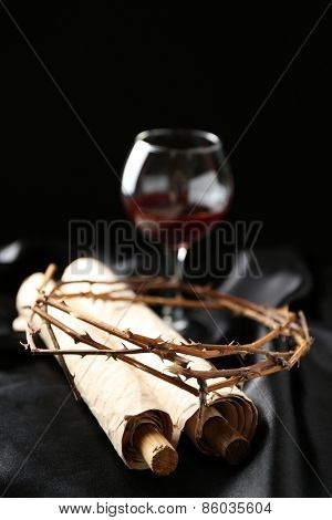 Crown of thorns, wine and old scroll on black background