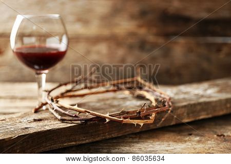 Crown of thorns and glass of wine on old wooden background