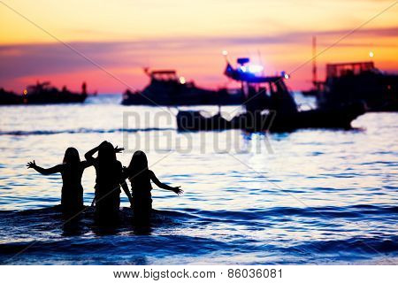 Girls playing in the water at sunset