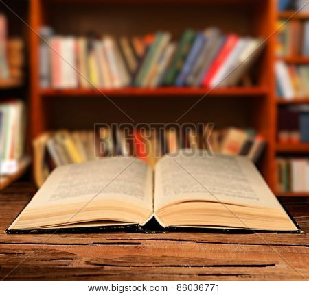 Open book on table on bookshelves background