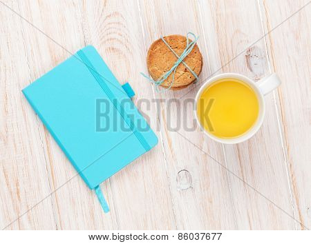 Cup of orange juice, gingerbread cookies and notepad on white wooden table with copy space