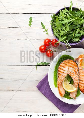 Grilled salmon and salad on wooden table. Top view with copy space