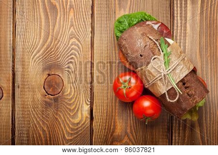 Sandwich with salad, ham, cheese and tomatoes on wooden table. Top view with copy space