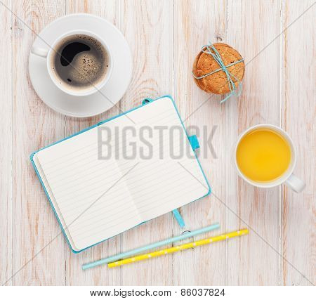 Cup of orange juice, coffee cup, gingerbread cookies and notepad on white wooden table with copy space