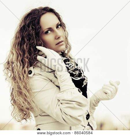 Sad beautiful fashion woman with long curly hairs outdoor