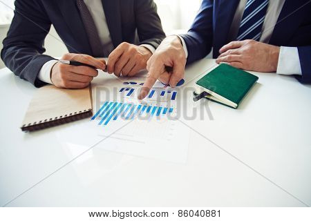 One man pointing to another man at diagram