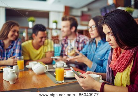 Four students eating and talking and one girl looking at telephone