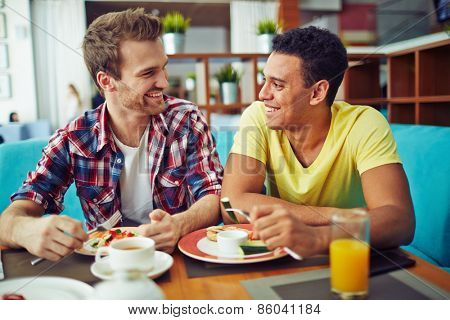 Two men eating and looking at each other