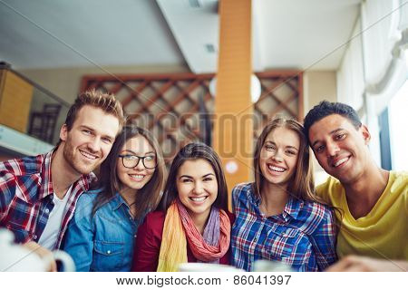 Five friendly young people looking at camera