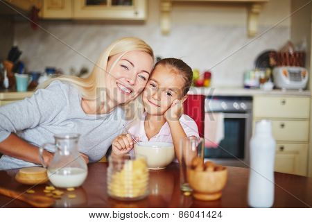 Happy mother and daughter sitting at table and looking at camera