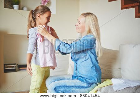 Careful mother fitting clothes on her daughter