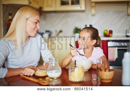 Mother and daughter smiling and looking at each other