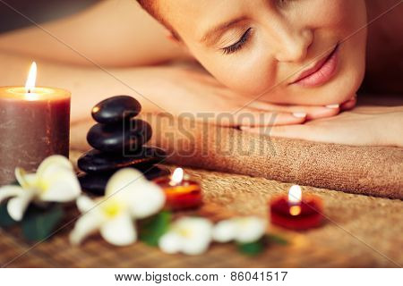 Close-up of female face among candles
