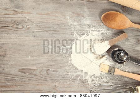 Baking tools from overhead view on wooden table in vintage tone, copy space on side.