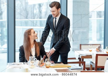 Business manager assists his colleague to stand up