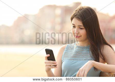 Pretty Girl Using A Mobile Phone In An Urban Park