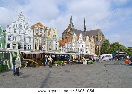 People walk by the New Market square in Rostock, Germany.