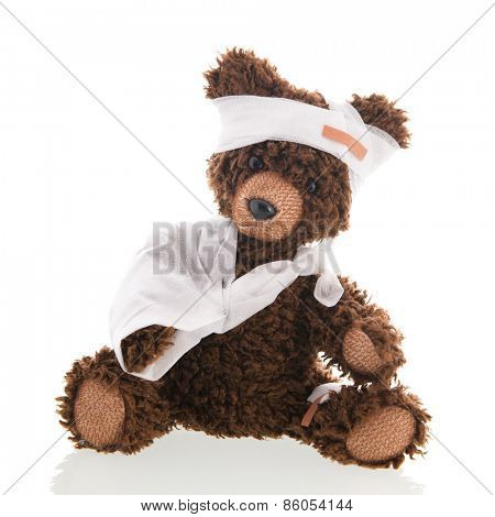 Stuffed hand made bear with pain and plaster isolated over white background
