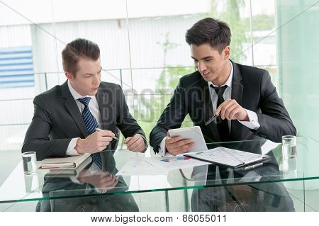 Two Businessman Using Tablet In Meeting
