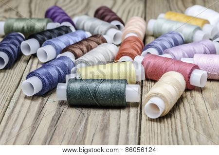 Multicolor sewing threads on wooden background