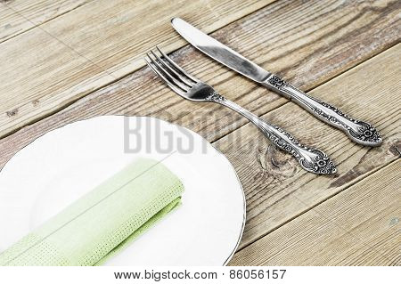 A white plate, a fork, a knife and a green napkin dining room  on a wooden background