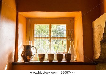 Small Window With Bottles, Jug And Cups In An Old Stone House, O
