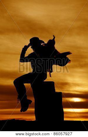 Silhouette Of Cowgirl With Saddle On Her Shoulder Sitting Looking Down