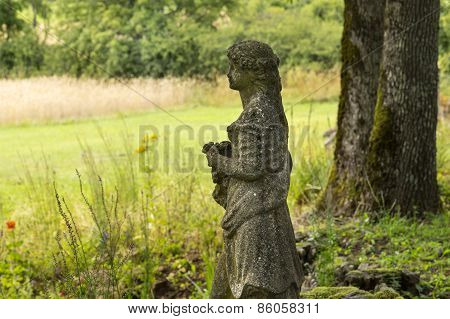 Ancient Stone Statue Of A Woman In An Old Garden
