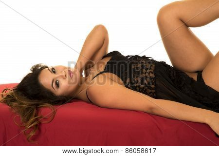 Woman In Black Nightgown On Red Sheet Lay On Back Close