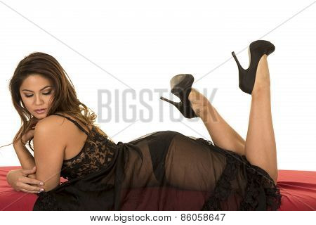 Woman In Black Nightgown On Red Sheet Laying On Stomach Legs Up