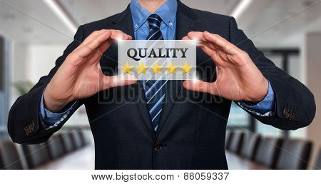 Businessman holding white card with Quality Five Stars sign