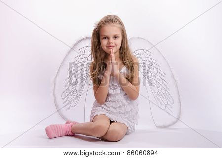 Sitting Girl In An Angel Costume With Folded Hands