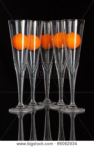 Five Glasses Of Champagne And Orange Golf Balls