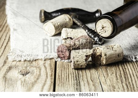 Close-up of corks, a corkscrew and  a wine bottle on a wooden  background  with a textile