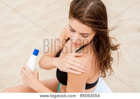 Young woman applying sunblock on the beach